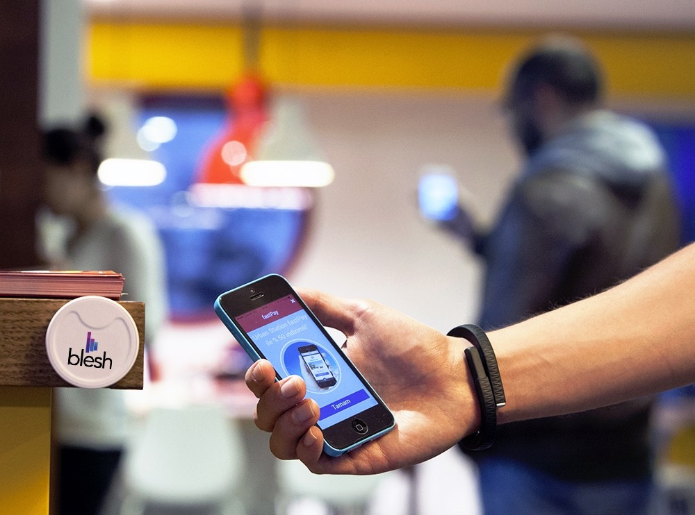 Man showing the Blesh app on his smartphone. Blesh initiated their Beacon tech more than two years ago. the number of Beacon users increased from 20,000 to 90,000 in the last two years.