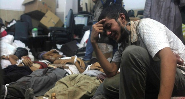 A man grieves as he looks at one of many bodies laid out in a make shift morgue after Egyptian security forces stormed two huge protest camps at the Rabaa al-Adawiya square. (AFP Photo)
