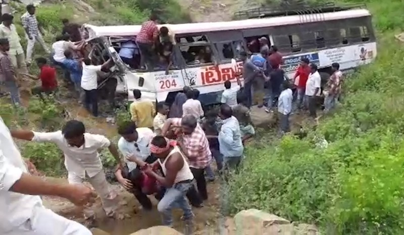 Screen grab made from video shows rescuers pull out passengers from a bus that fell into a gorge in Jagtiyal district of Telangana, India, Tuesday, Sept. 11, 2018. (AP Photo)