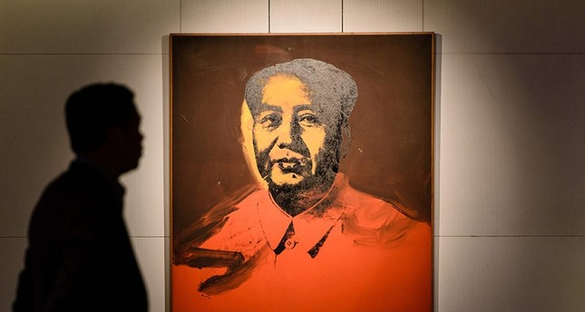 This file photo taken on March 17, 2017 shows a man walking past 'Mao' by US artist Andy Warhol, 1973, an acrylic and silkscreen ink on canvas, during a pre-auction preview by Sotheby's in Hong Kong. (AFP Photo)