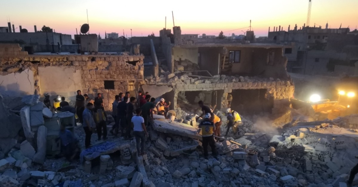 Rescue teams search for survivors under the remains of houses turned to rubble with Assad regime airstrikes. (AA Photo)