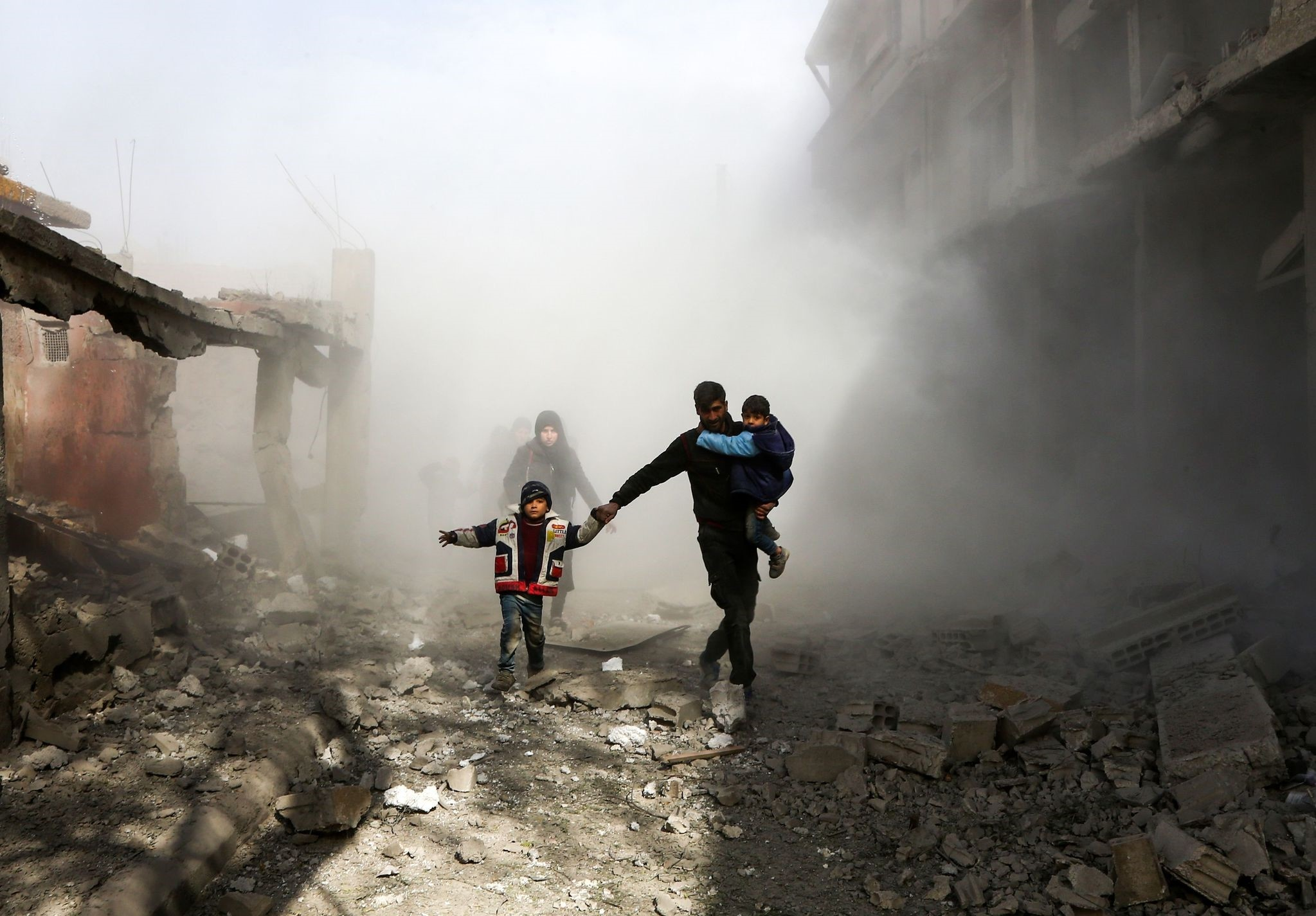 Syrian civlians flee from reported regime air strikes in the rebel-held town of Jisreen, in the besieged Eastern Ghouta region on the outskirts of the capital Damascus, on February 8, 2018. (AFP Photo)