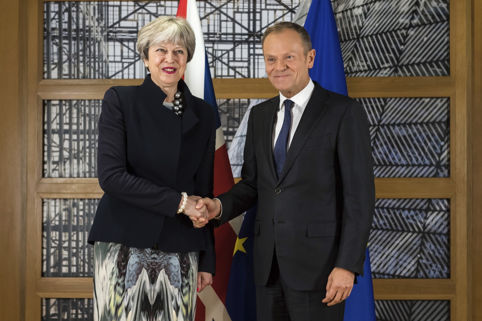 British Prime Minister Theresa May, left, shakes hands with European Council President Donald Tusk at the Europa building in Brussels on Monday, Dec. 4, 2017. (AP Photo)