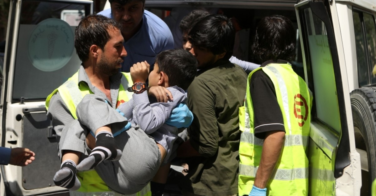 An Afghan health worker carries a wounded school student after a car bomb blast targeted a governmental institution in downtown Kabul, Afghanistan, July 1, 2019. (AP Photo)