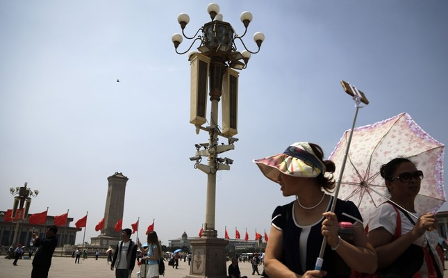 Tourists gather near a pole with security cameras attached to monitor Tiananmen Square in Beijing. Chinese authorities are maintaining a tight security around Tiananmen Square ahead of anniversary of deadly 1989 crackdown on pro-democracy protesters.