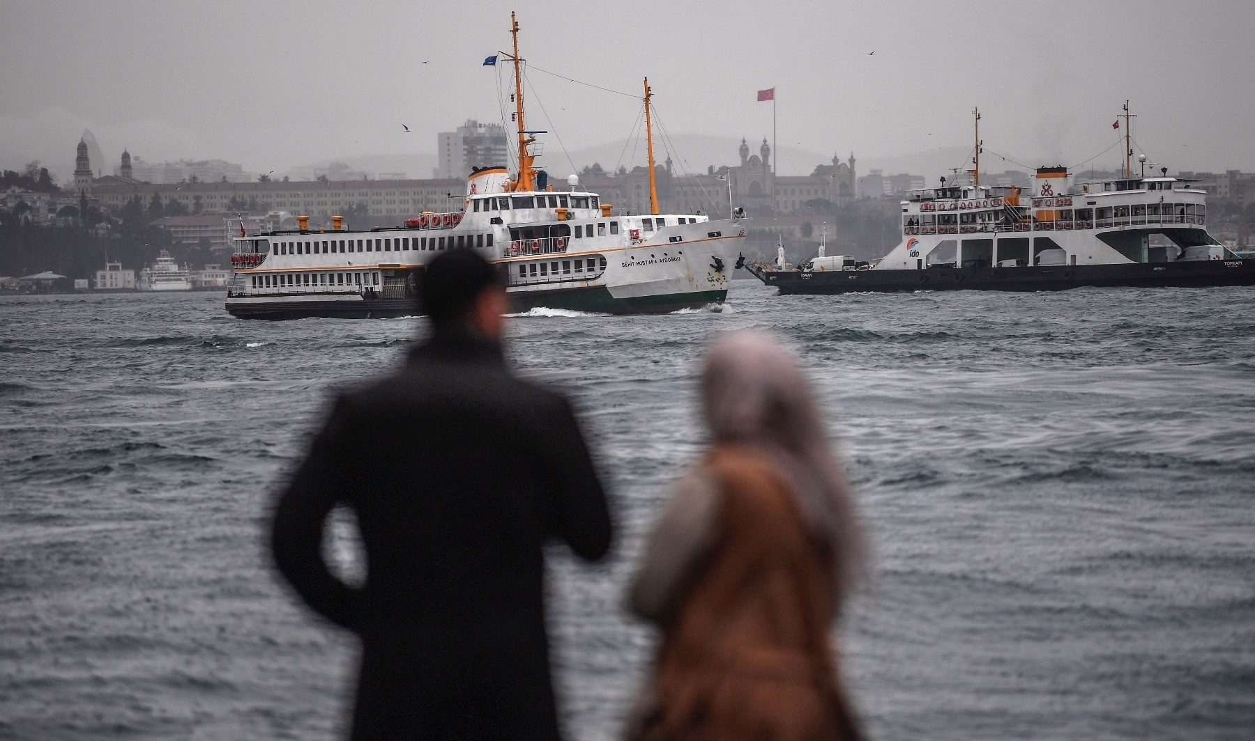A Turkish couple awaits a ferryboat near the Bosporus strait on a rainy and windswept morning in the Karaku00f6y district of Istanbul, Jan. 11.