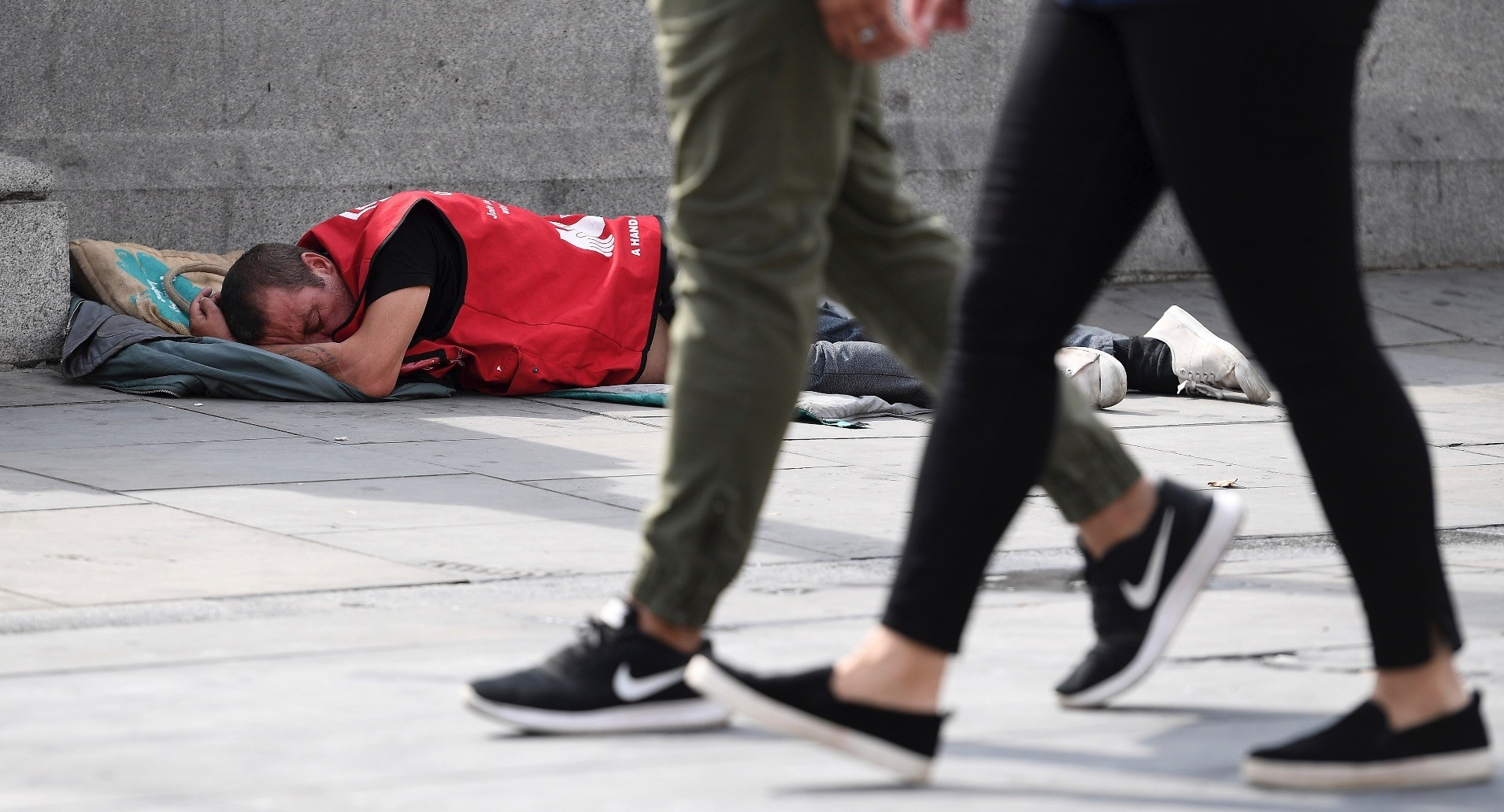 A homeless man takes a nap on a pavement in downtown London.