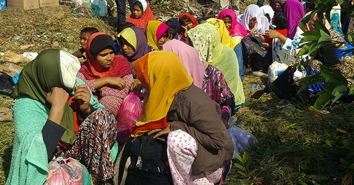 Rohingya refugees, who landed on an isolated northern shore near the Malaysia-Thai border, huddle in a group in Kangar on March 1, 2019, following their detention by Malaysian immigration authorities. (AFP Photo)