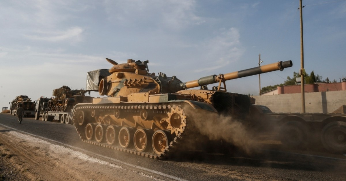 A Turkish forces tank is driven to its new position after was transported by trucks, on a road towards the border with Syria in Sanliurfa province, Turkey, on Monday, Oct. 14, 2019. (AP Photo)