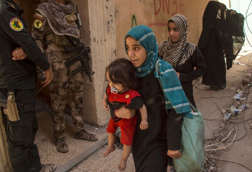 Civilians flee as members of Iraq's Counter-Terrorism Service (CTS) advance in the old city of Mosul yesterday, amid an' ongoing government offensive to retake the city from Daesh.