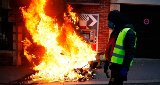 A Yellow Vest (Gilets jaunes) anti-government protester walks past burning material near an ATM during during clashes with security personnel on a street in Rouen, north-western France on January 5, 2019. (AFP Photo)