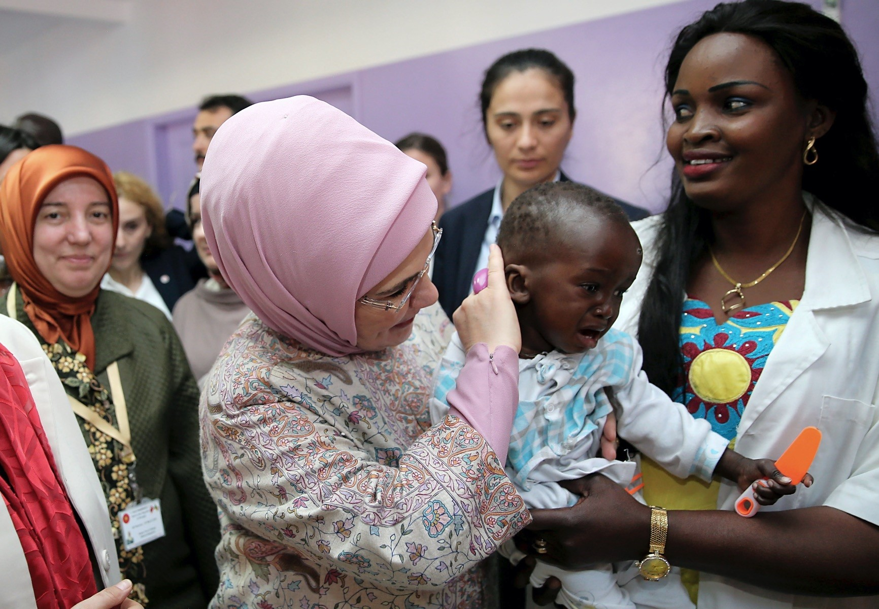 Turkish first lady Emine Erdou011fan gently caresses a Senegalese baby during her visit to a Turkey-sponsored school in Dakar, March 1.