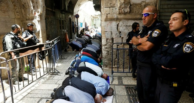 Palestinian men pray as Israeli security forces secure the Al-Aqsa mosque compou   nd in Jerusalem's Old City, July 26.