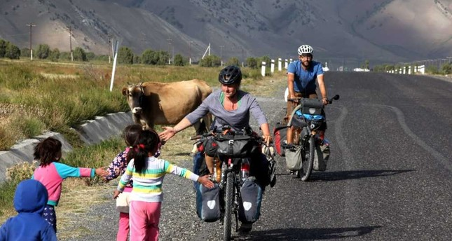 Cyclists Christian Pries (R) and Maren Hagel are greeted by the local children during their journey through Turkey.
