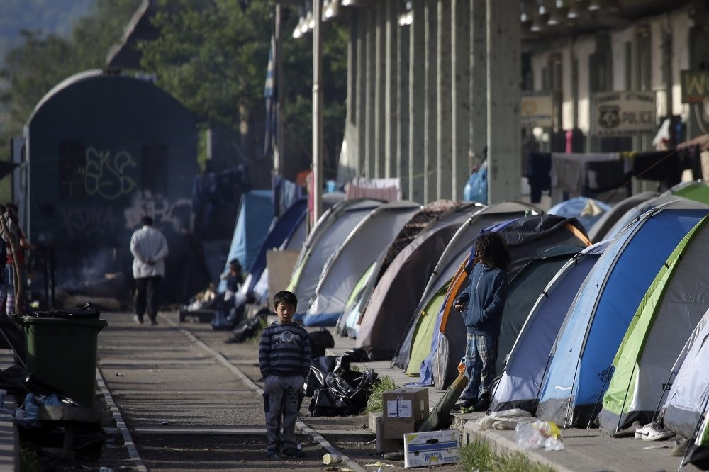 Children stand outside their tents set on the platform of a railway  station turned  makeshift camp for migrants and refugees at the northern Greek border point of Idomeni, Greece, April 28, 2016.