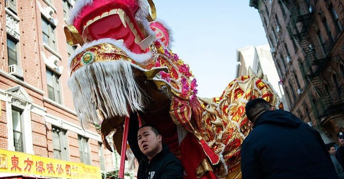 A man carries a dragon costume as people prepare for the Chinese New Year parade in Manhattan's Chinatown, in New York City, February 22, 2015.