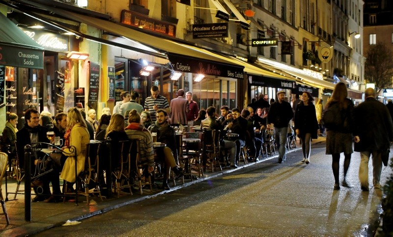 People sit at tables outside a bistro in Paris. (REUTERS Photo)