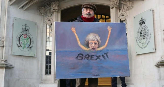 Satirical artist Kaya Mar poses with a Brexit-themed artwork depicting British PM Theresa May, as he stands outside the Supreme Court in London in January (AFP Photo)