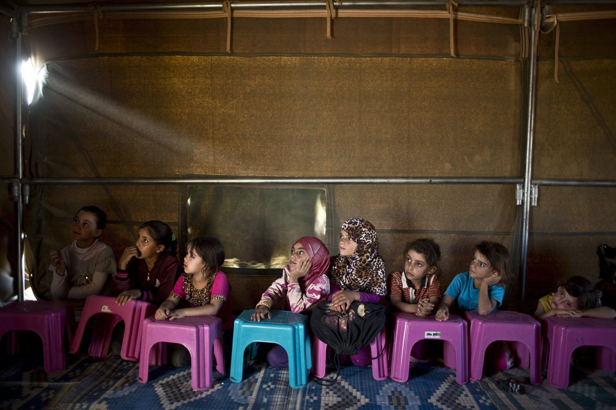 Syrian refugee children attending a class at a makeshift school set up in a tent at an informal tented settlement near the Syrian border on the outskirts of Mafraq, Jordan, Oct. 21, 2015. (AP Photo)