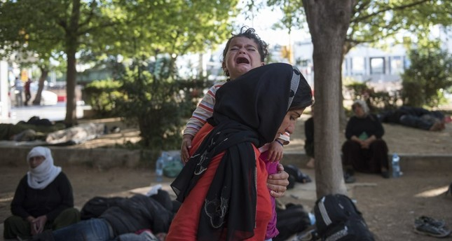 A woman carries her crying baby in a park in the northern Greek city of Thessaloniki, July 9.