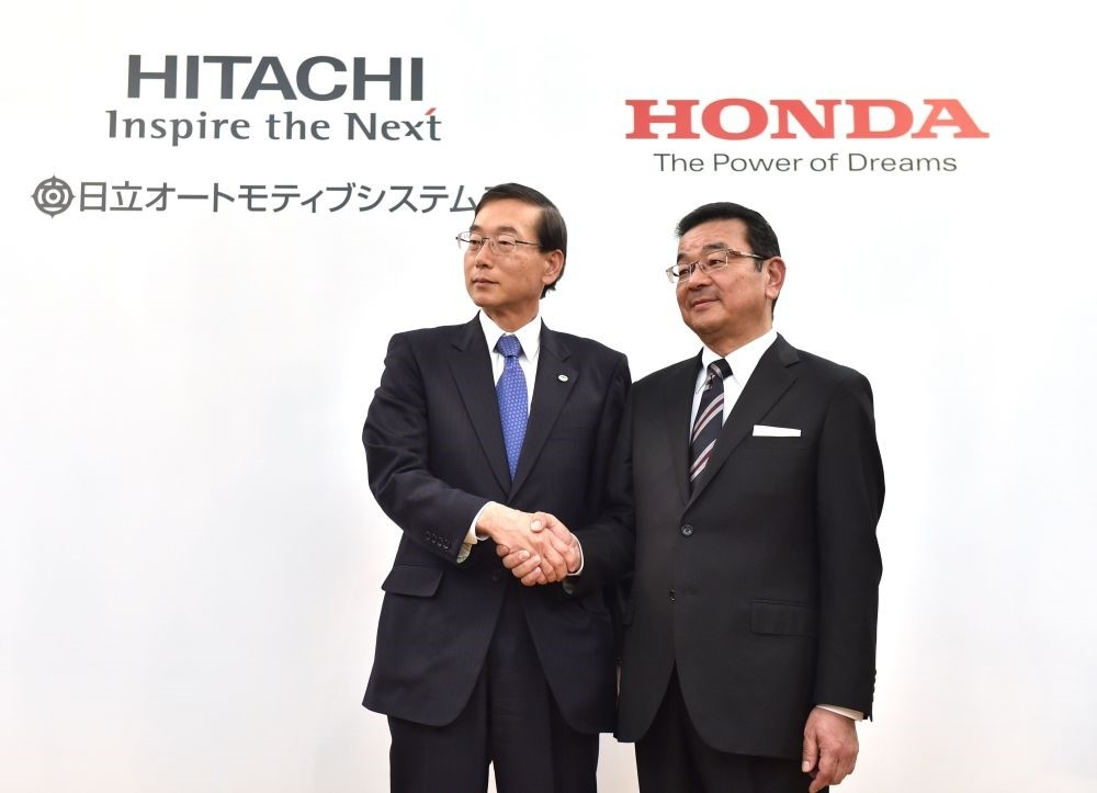 Honda Motor President, CEO and representative director Takahiro Hachigo (R) shakes hands with Hitachi Automotive Systems President and CEO Hideki Seki (L) following their joint press conference in Tokyo.