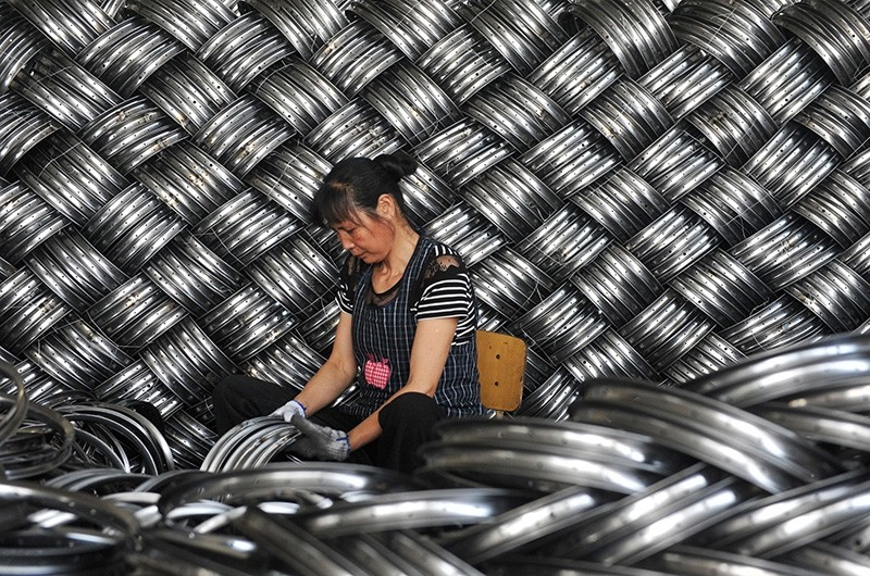 A worker checks wheel hubs of baby carriages that will be exported at a factory in Hangzhou in China's eastern Zhejiang province on June 4, 2018. (AFP Photo)