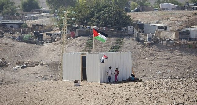 Palestinian girls stand by a newly made shed in the West Bank Bedouin community of Khan al-Ahmar, Sept. 11.