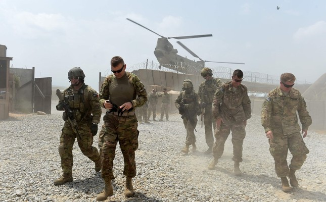 U.S. soldiers walk as a NATO helicopter flies overhead  at coalition force Forward Operating Base (FOB) Connelly in the Khogyani district in the eastern province of Nangarhar, Afghanistan, Aug. 12, 2015.