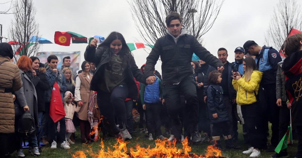 People leap over flames at a Nevruz event in Istanbul, March 21, 2019.