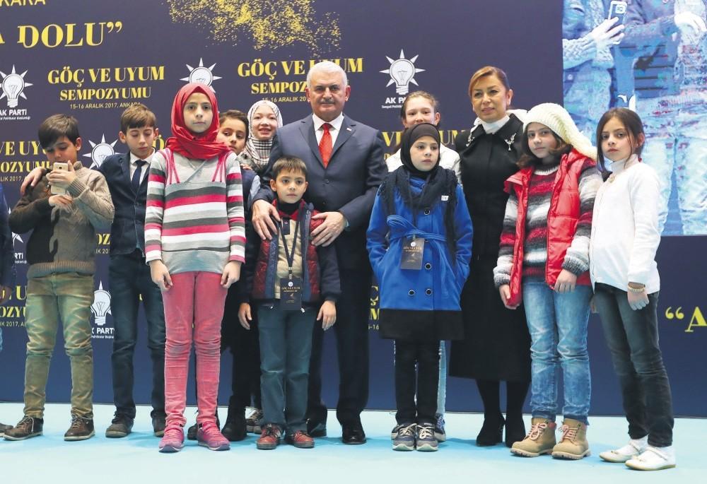 Prime Minister Binali Yu0131ldu0131ru0131m poses with refugee children at the symposium in Ankara.