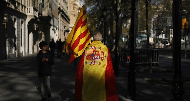 A man wearing a Spanish flag walks along a street ahead of a rally against Catalonia's declaration of independence, in Barcelona, Spain, Sunday, Oct. 29, 2017 (AP Photo)