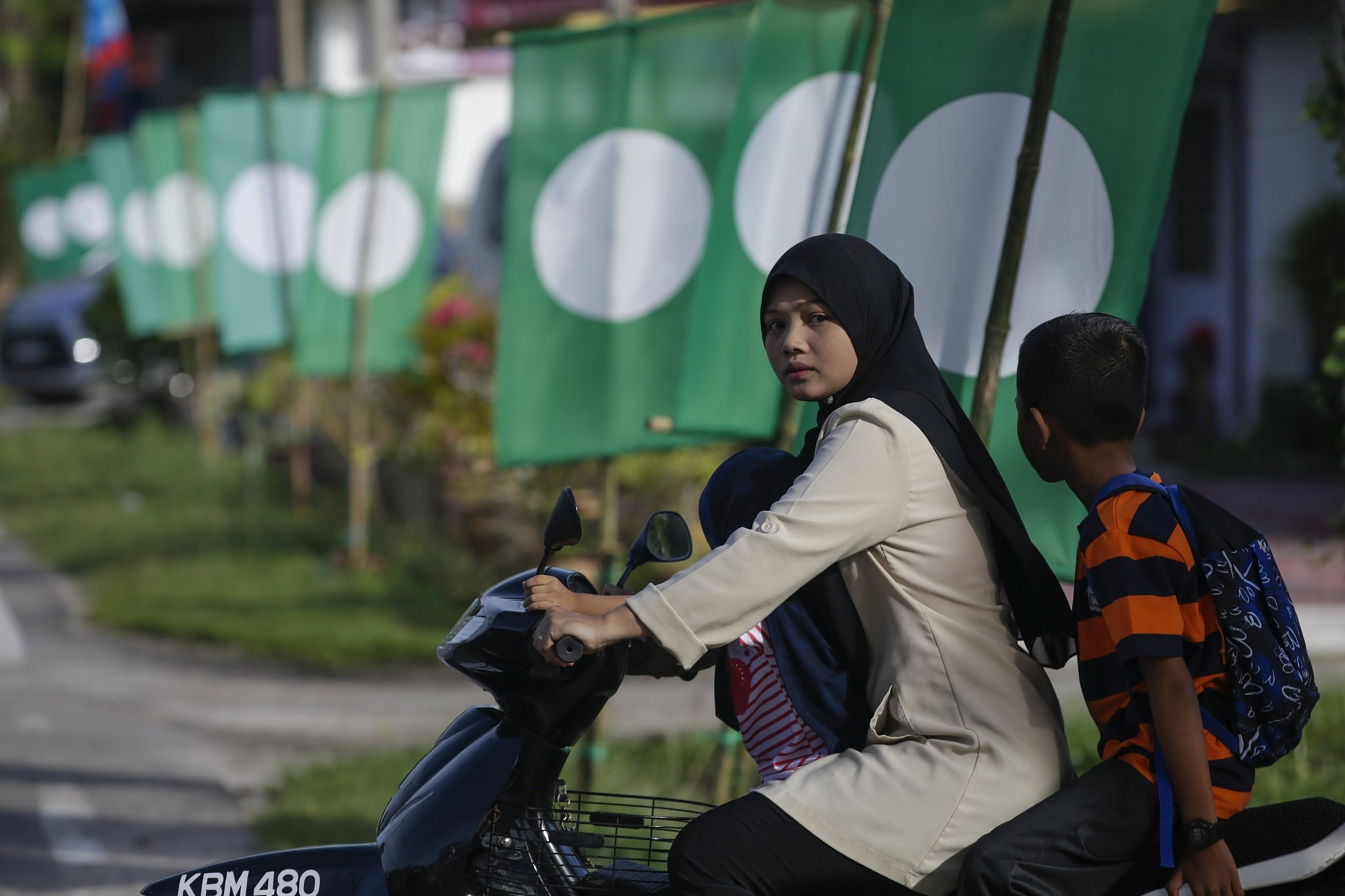 A mother and her son ride a motorcycle in front of Pan Malaysian Islamic Party (PAS) flags on the island of Langkawi, Malaysia, April 27.