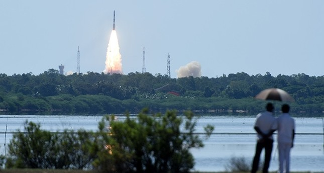 Bystanders watch as Indian Space Research Organisation's (ISRO) satellite CARTOSAT-2, along with 20 other satellites (AFP Photo)