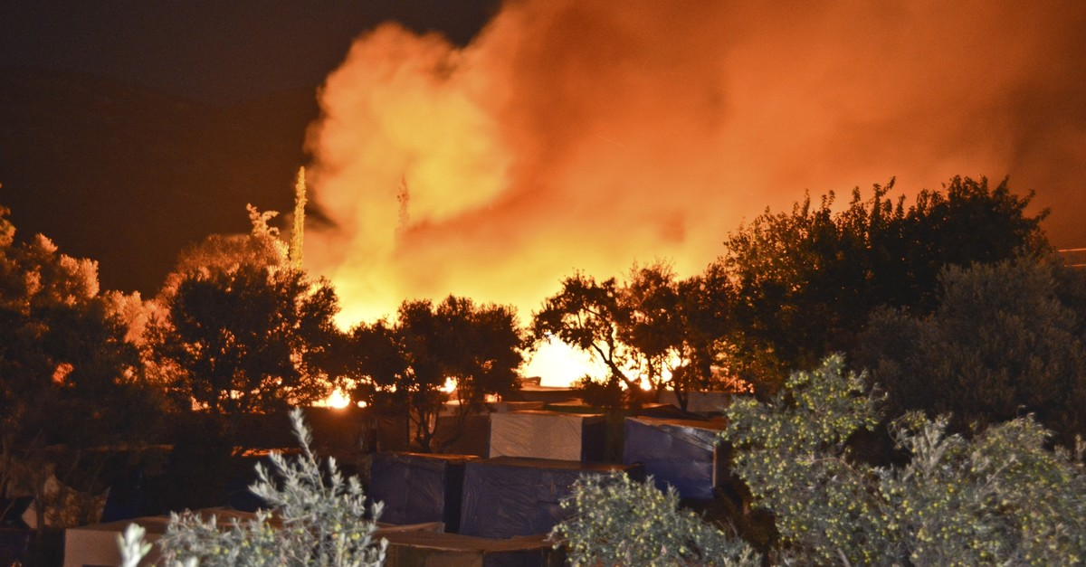 A fire burns behind makeshift tents used by asylum-seekers in Samos Island Greece, late Monday, Oct. 14, 2019. (AP Photo)