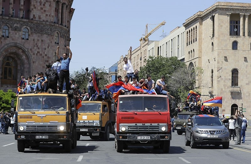 Supporters of opposition lawmaker Nikol Pashinian react standing on top of vehicles as they protest in Republic Square in Yerevan on Wednesday, May 2, 2018. (AP Photo)