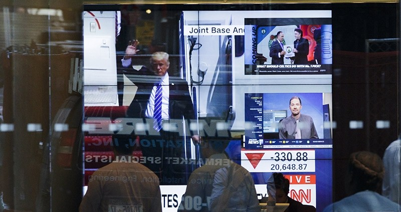 President Donald Trump is show on a live television broadcast arriving back to Washington DC as a graphic shows the Dow Jones industrial average down 330 points (EPA Photo)