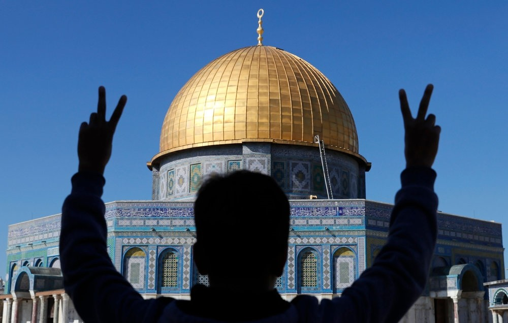 A Palestinian youth flashes the V for victory sign during Friday prayers in front of the Dome of the Rock at the Al-Aqsa Complex in Jerusalem's old city, Dec. 8, 2017.
