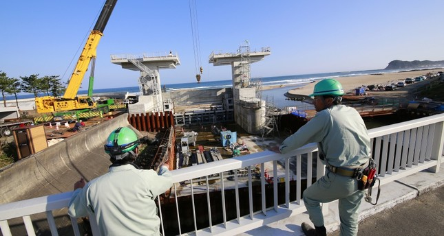 Workers look at a floodgate under construction after a tsunami warning was lifted, in Iwaki, Fukushima prefecture.