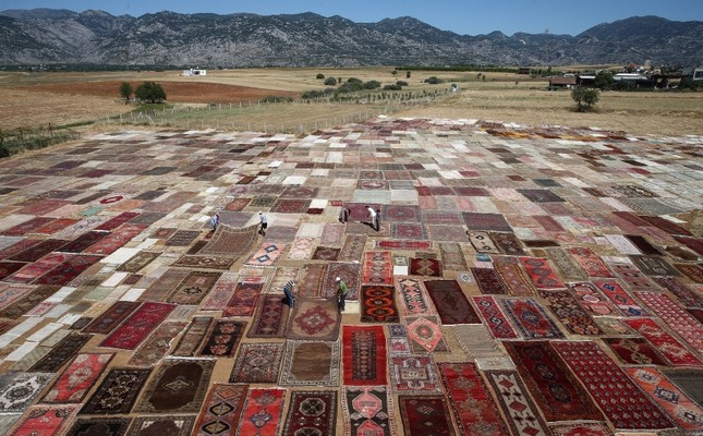 Summer rays in Turkey's Antalya clean and color hand-woven carpets