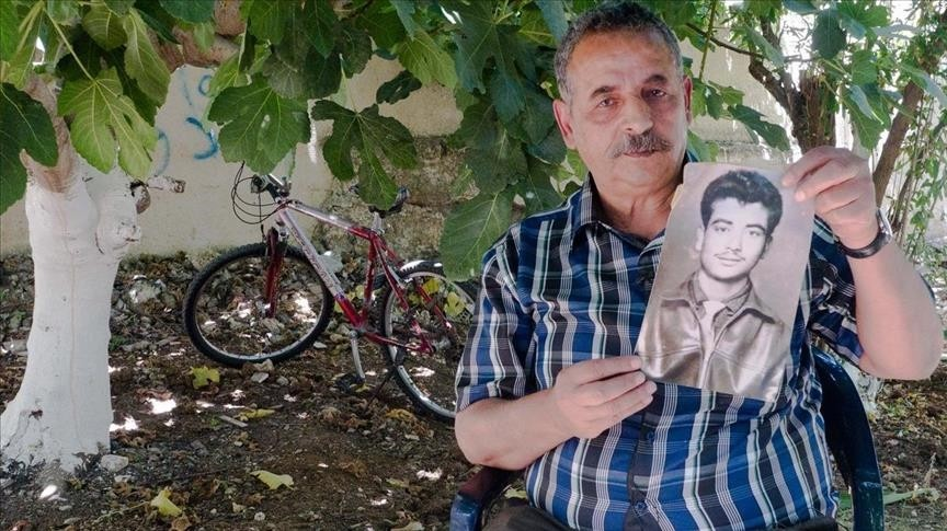 Hassan Dawleh holding a picture of his brother Anis Dawleh, who died in prison in 1982.