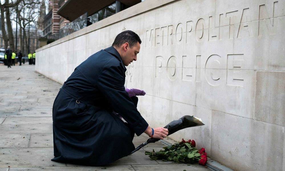 A member of the public lays flowers outside New Scotland Yard in central London, Britain, March 23.