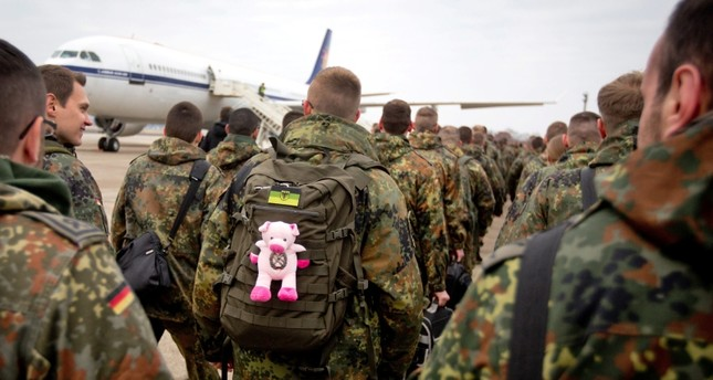A German soldier has a stuffed animal - a small pig as a lucky charm - attached to his backpack as a contingent of  German soldiers prepares to leave for Turkey, on the military part of the Tegel airport in Berlin, Germany, 20 Jan. 2013. (EPA Photo)