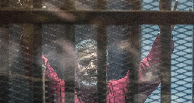 In this file photo taken on April 23, 2016 Egypt's ousted president Mohamed Morsi, wearing a red uniform, gestures from behind the bars during his trial in Cairo at the police academy. (AFP Photo)