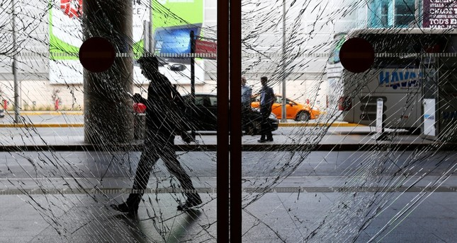 A man walks behind shattered glass at Istanbul's Atatürk International Airport, following Tuesday's blast, June 29.