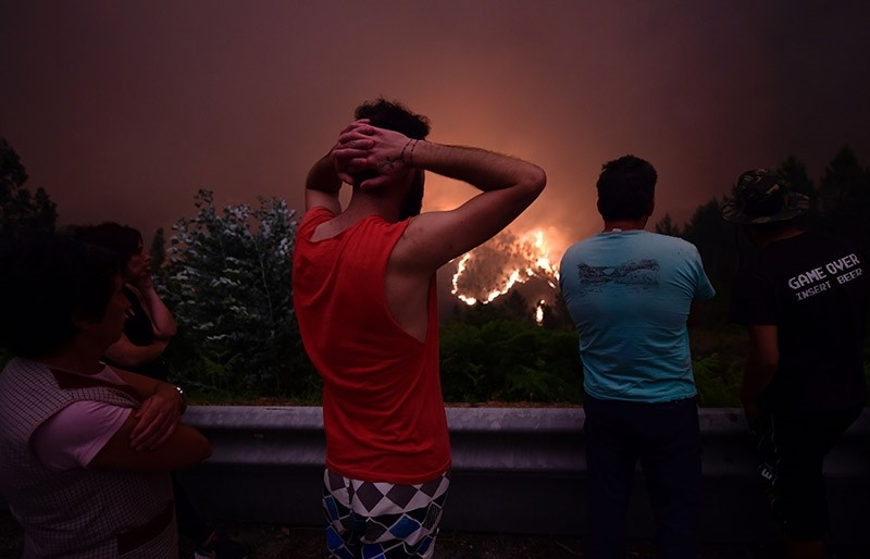 Villagers look at flames during a wildfire near the village of Mega Fundeira on June 18, 2017. (AFP Photo)