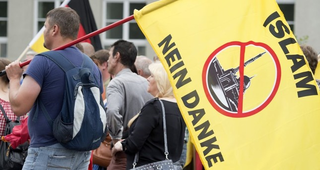 A supporter of the right-wing Patriotic Europeans say NO, holds a flag reading: Islam, No Thanks, during a rally in Erfurt, Germany, June 4, 2016.