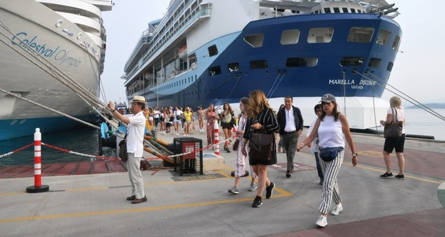 The Bahamas-flagged Marella Discovery cruiser (R) with 2,846 passengers was one of four cruise ships that docked at Ege Port in Kuşadası, June 11, 2019.