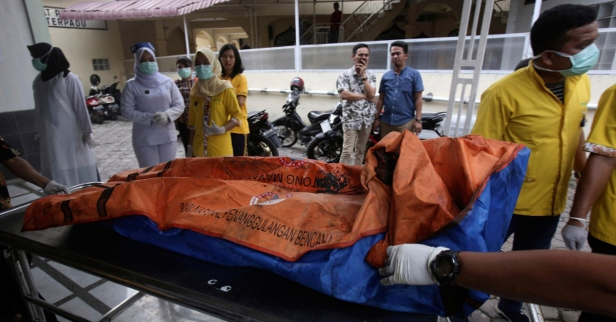 Paramedics put body bags containing the remains of the victims of a fire that razed through a match factory on a stretcher upon arrival at a hospital in Medan, North Sumatra, Indonesia, Friday, June 21, 2019. (AP Photo)