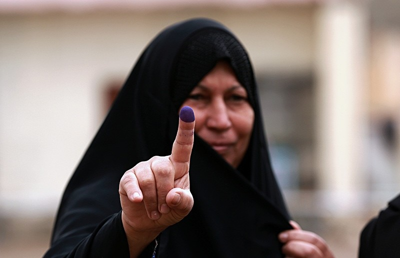 In this May 12, 2018 file photo, an Iraqi woman shows her ink-stained finger after casting her vote in the country's parliamentary elections in Ramadi, Iraq. (AP Photo)