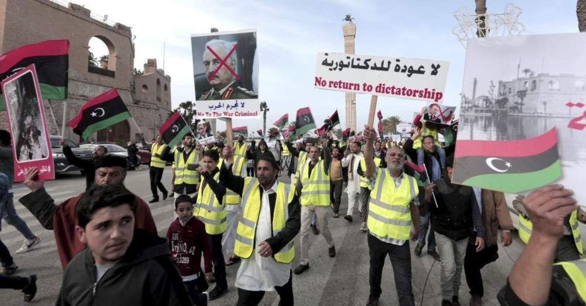 In this April 19, 2019 file photo, protesters wear yellow vests at a protest as they wave national flags and chant slogans against Libya's Field Marshal Khalifa Hifter, in Tripoli, Libya. (AP Photo)